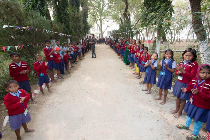 Schoolchildren line up to receive Thaye Dorje, His Holiness the 17th Gyalwa Karmapa, at the Bodhi Tree school