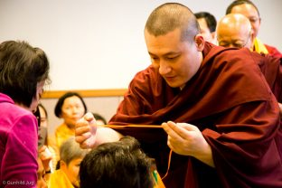 Thaye Dorje, His Holiness the 17th Gyalwa Karmapa, gives a blessing string to a student