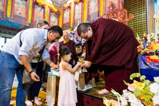 Thaye Dorje, His Holiness the 17th Gyalwa Karmapa blesses a child during the Chenresig empowerment at the KIBI Public Course