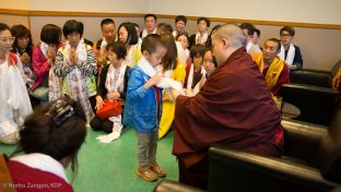 Thaye Dorje, His Holiness the 17th Gyalwa Karmapa, blesses a small child with a katak (ceremonial scarf)