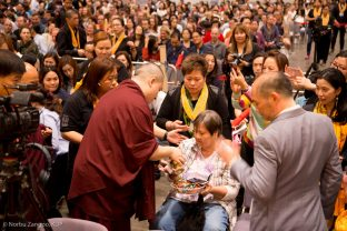 A student receives a blessing from Thaye Dorje, His Holiness the 17th Gyalwa Karmapa, at the Chenresig empowerment in Hong Kong
