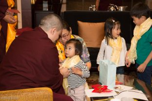 A small child is blessed by Thaye Dorje, His Holiness the 17th Gyalwa Karmapa