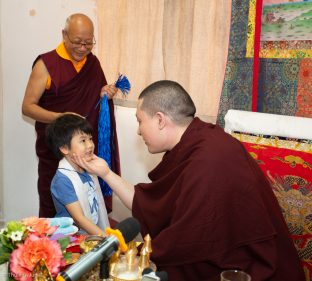 Students and visitors make symbolic offerings and receive blessings at the Bodhi Path Tara Buddhist Centre of Lama Jakarla in Hong Kong. Solponla, Karmapa's senior attendant, smiles in the background