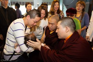 Thaye Dorje, His Holiness the 17th Gyalwa Karmapa, and His Eminence 4th Jamgon Kongtrul Rinpoche bless a small child