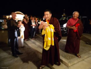 Karmapa cradles Thugsey (his son), with Jigme Rinpoche, Karmapa's General Secretary, smiling in the background
