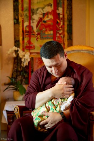 Thaye Dorje, His Holiness the 17th Gyalwa Karmapa, gently cradles Thugsey (his son)