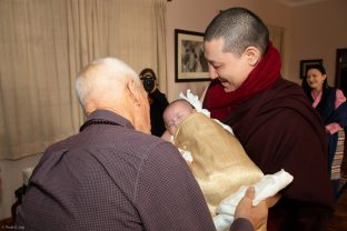 Karmapa holds Thugsey, with Lama Ole looking on affectionately. Sangyumla Rinchen Yangzom is in the background.