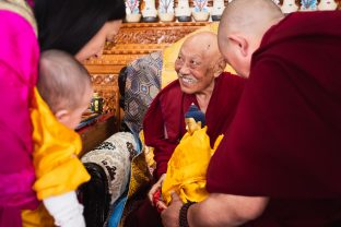 The compassion and wisdom of His Eminence Luding Khenchen Rinpoche emanates from his smile as he offers little Thugsey and Sangyumla a Buddha
