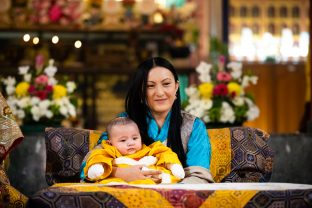 Sangyumla Rinchen Yangzom tenderly holds little Thugsey in the temple at KIBI.