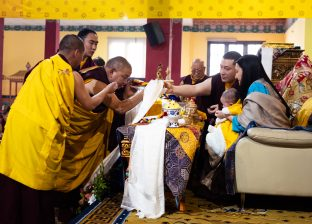 Everyone present at the Public Meditation Course lined up to offer a white scarf (khata) to Karmapa, and then to Thugsey (held by Sangyumla)