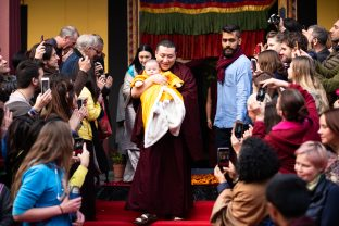 The students capture a special moment as Karmapa gently carries his son at KIBI. Sangyumla follows closely behind