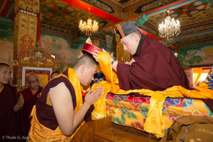 Thaye Dorje, His Holiness the 17th Gyalwa Karmapa, presents the red hat of activity to HE Jamgon Kongtrul Rinpoche at the Kagyu Monlam 2016
