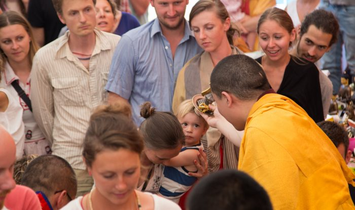 Thaye Dorje, His Holiness the 17th Gyalwa Karmapa, blesses a mother and child at a Dharma course. Photo / Magda Jungowska