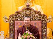 Thaye Dorje, His Holiness the 17th Gyalwa Karmapa, in front of a statue of the Buddha