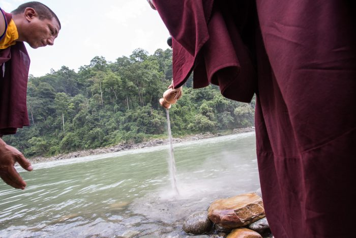 Pouring a mandala offering into the river on the 3rd anniversary of the parinirvana of His Holiness Kunzig Shamar Rinpoche. Photo / Magda Jungowska